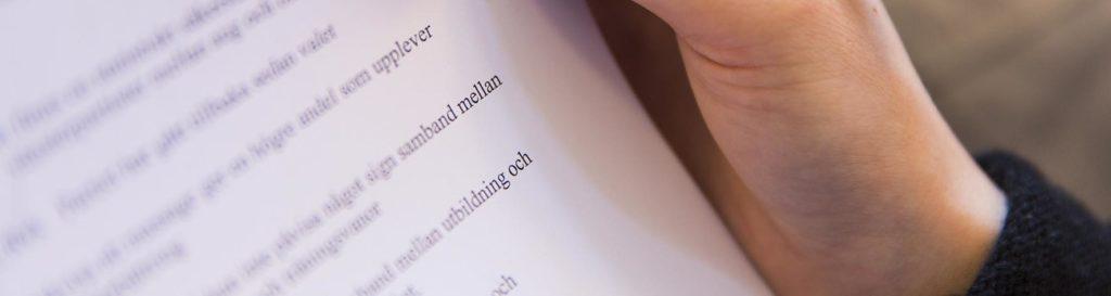 Hand som håller ett papper med text